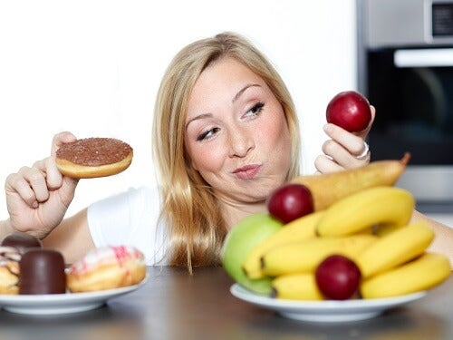 Woman dithers between fruits or sweets