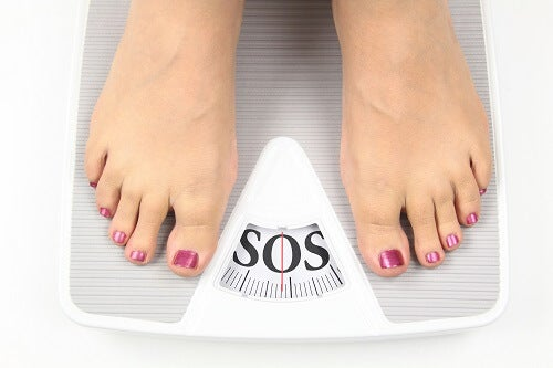 Person weighing themselves on scales
