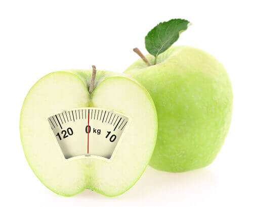 An apple with a scale demonstrating losing weight
