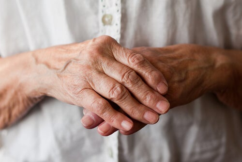 An elderly person putting one of their hands on the other.