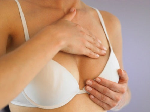 Woman touching her breasts to detect possible causes of breast pain