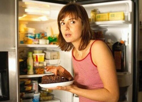 Woman sneaking food from fridge