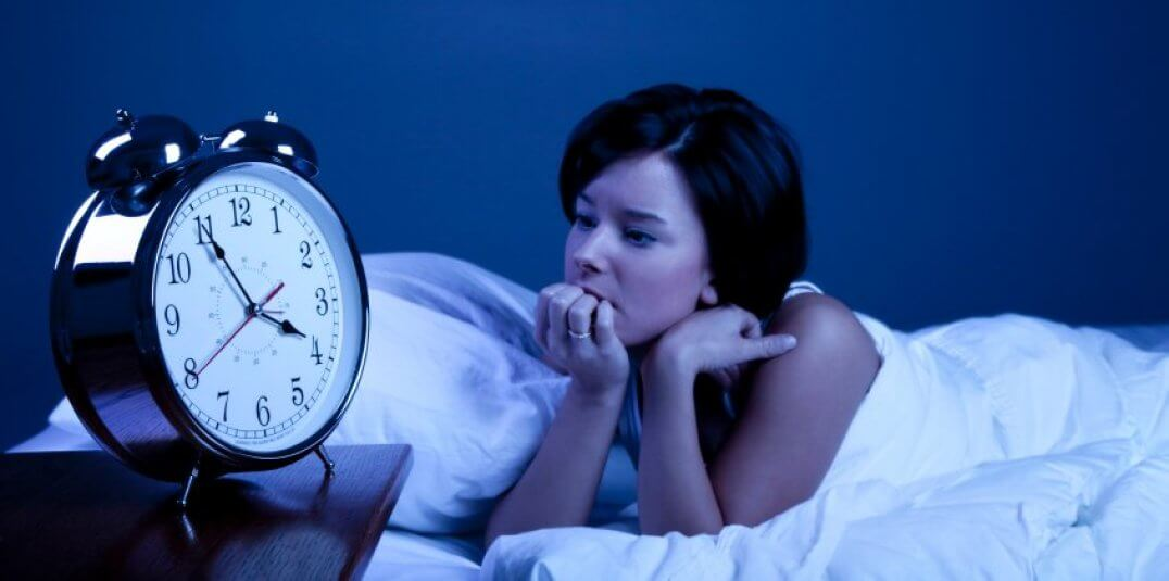 Woman with insomnia looking at the clock