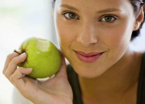 Woman eating an apple to get rid of flab