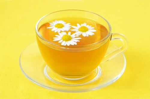A glass cup with chamomile tea.