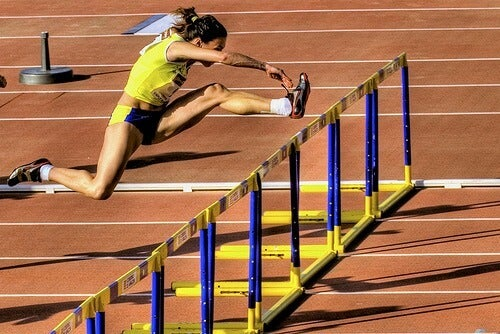 A woman jumping hurdles