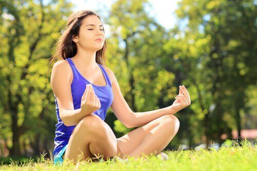 Woman meditating in the grass increasing your self-esteem
