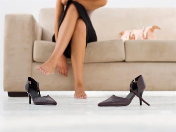 A woman taking her shoes off.