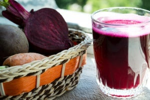 Basket with beets and glass of beet juice on a table
