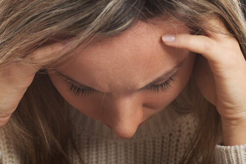 woman with emotional problems holding her head