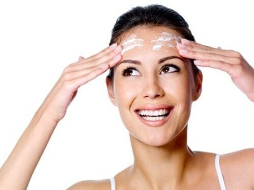 A woman applying a face cream.
