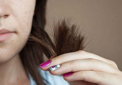 Woman holding dry ends of her hair