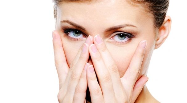 Woman touching her face near her eyes