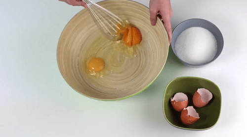A person beating eggs to make the yogurt sponge cake recipe.