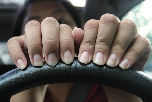 Woman with hands on steering wheel really needs a manicure nails peel long and uneven nails