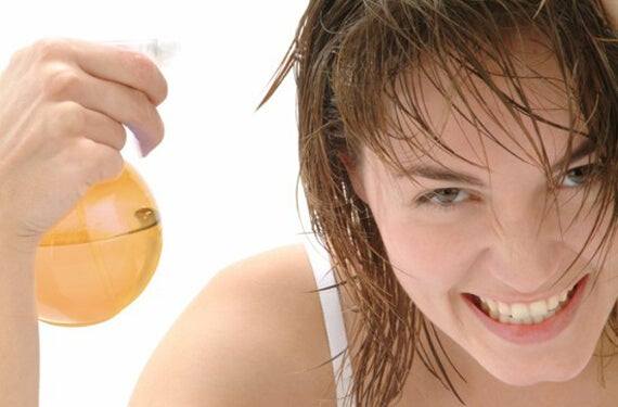 Woman applying a hair loss lotion