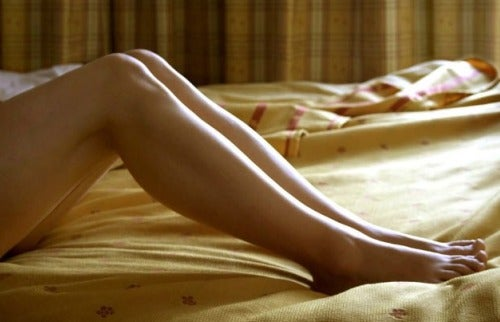 The legs of a lady lying on bed.