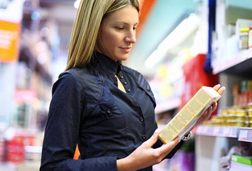Woman looking at packet in supermarket