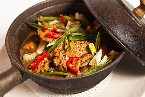 A pan with chicken and vegetables.