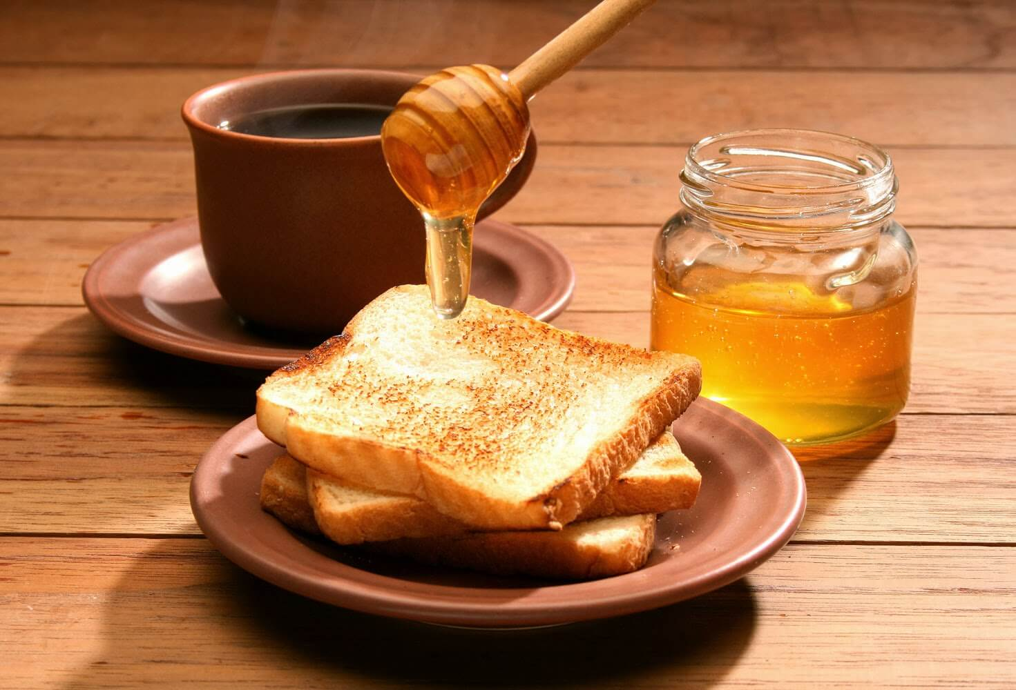 Pouring some honey on a toast.