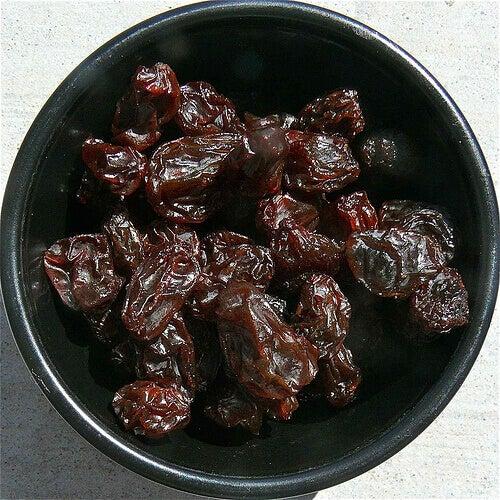 Raisins in a black colored bowl white background benefits of raisins