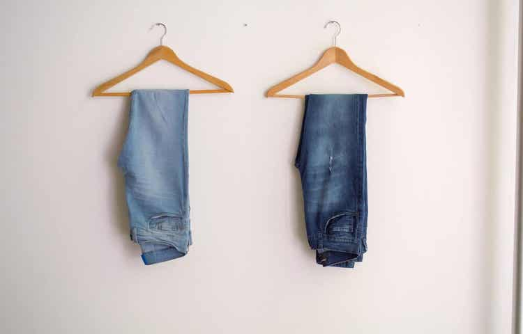 Jeans hanging on hangers.