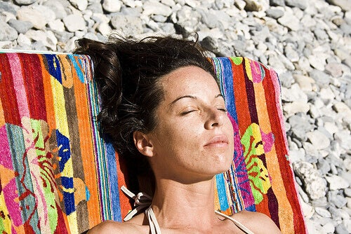 Woman sunbathing on a pebble beach strengthen your immune system