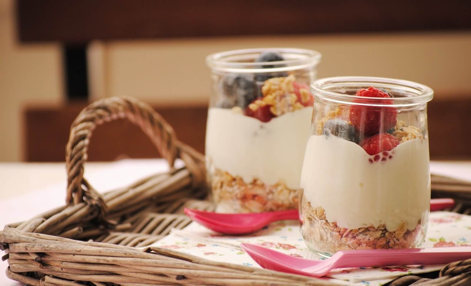 Two yoghurts with fruit and cereals.