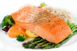 A plate of salmon with vegetables.