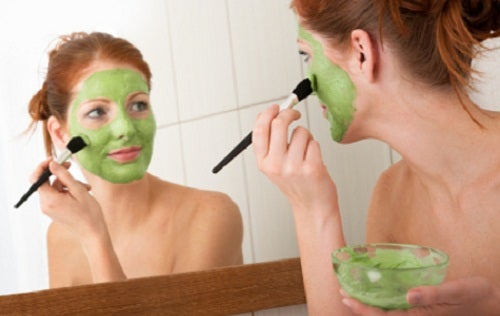 woman applying a clay mask