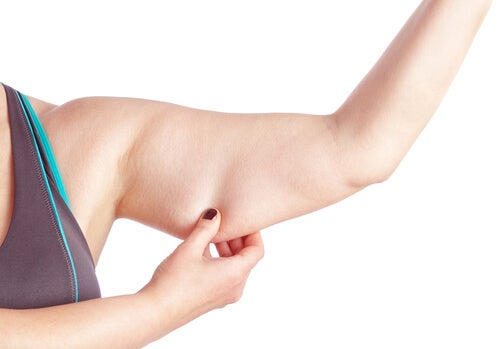 Woman holding loose skin of her arm