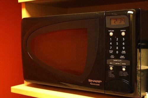 Black microwave on a white shelf