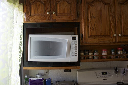 White microwave with wood cupboards