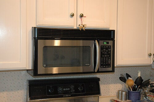 Stainless steel microwave with white cupboards