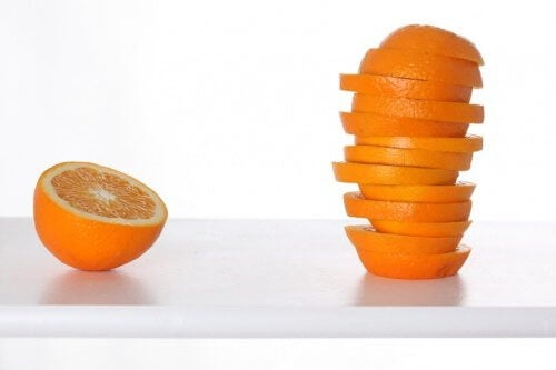 Half an orange next to stack of slices