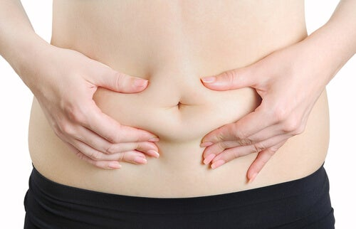 A person squeezing their abdominal fat.