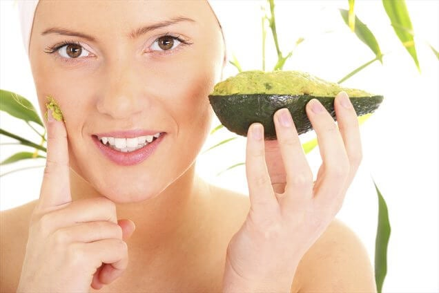 Woman applying an avocado mask