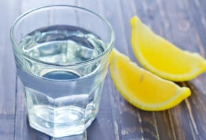 Glass of water on table with slices of lemon beside it drinking lemon water