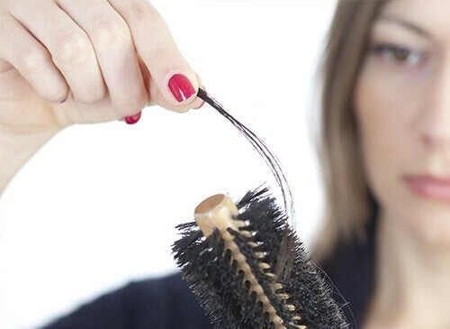 Woman pulling hair off of brush