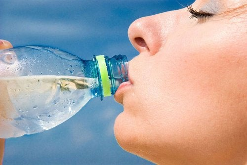 A woman drinking from a bottle of water