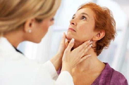 A doctor checking the thyroid of a woman.