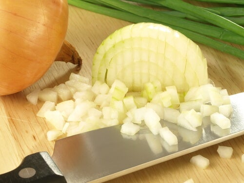 A knife with some diced onion.