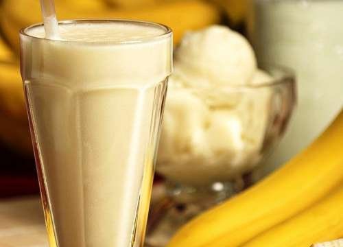 A banana smoothie with ice cream in a glass.