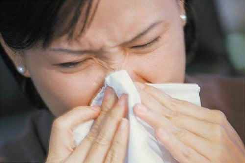 Woman sneezing into a tissue ways to stop snoring