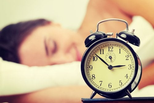 Woman sleeps with alarm clock in foreground sleep poorly