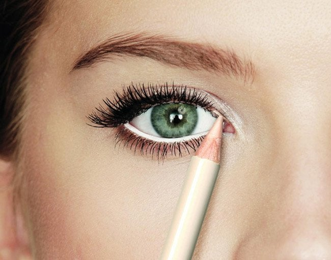 Woman applying white eyeliner to her waterline