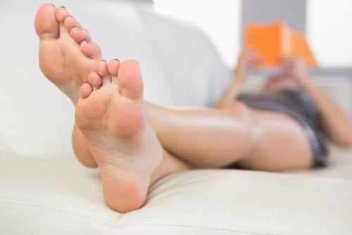 Woman sitting on couch reading with feet up harm your heels