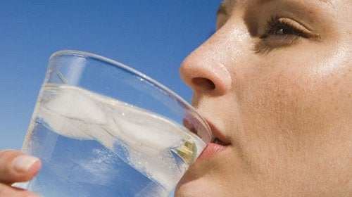 Lady drinking a glass of water with ice