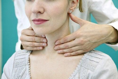 Lääkäri koettelee naisen kaulaa