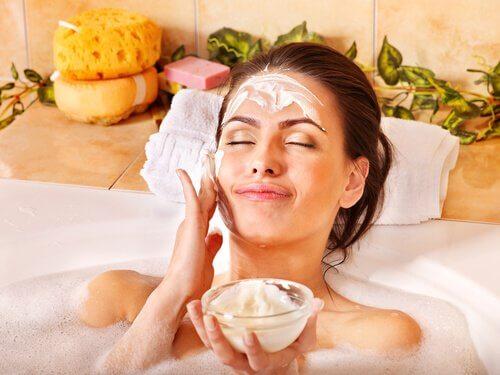 Nainen on kylvyssä ja laittaa naamioita kasvoihinsa